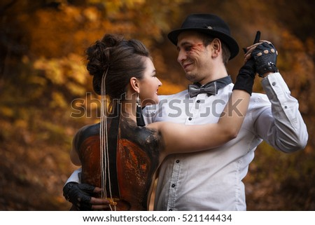 Stock Photo Young woman with man pair hugging in dancing pose. Woman has violin painting on her skin back.
