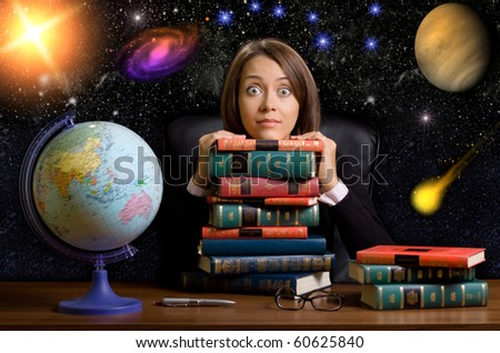 young woman with many books at the desk on space background