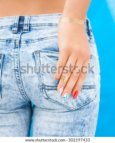 Young woman with marine sailor gel nails manicure holding hand at jeans back pocket