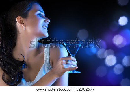 Young woman with martini glass in blue light on holiday background