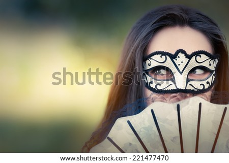 Young Woman with Mask and Fan - Portrait of a mysterious masked woman holding a fan