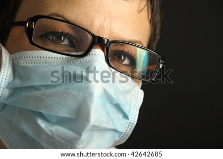 Young woman with medical mask. Virus concept. Studio shot. Black background.