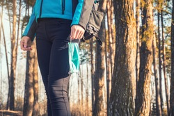 young woman with medical mask walks in her hands. spring pinewood. safe walk. Coronavirus covid19