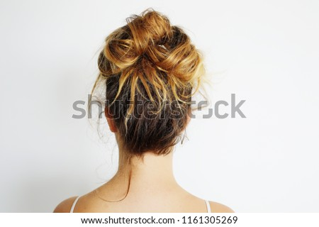 Young woman with messy bun hairstyle.