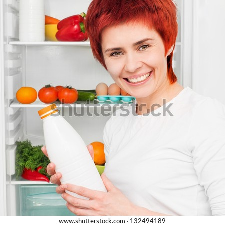 young woman with milk against the refrigerator with food