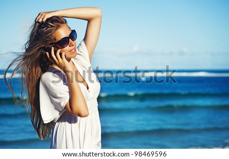 young woman with mobile phone on a beach, bali #98469596