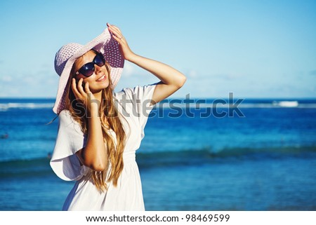 young woman with mobile phone on a beach, bali
