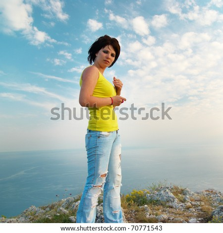 Young woman with mobile phone on cloudscape background