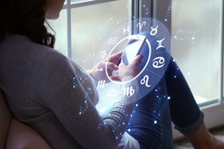 Young woman with mobile phone reading astrological forecast at home