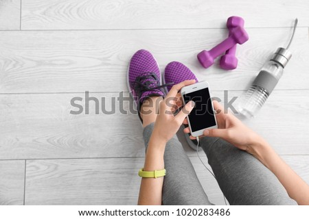 Young woman with mobile phone sitting near dumbbells on floor, flat lay. Ready for gym workout