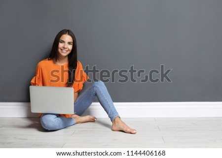 Young woman with modern laptop sitting on floor near grey wall #1144406168