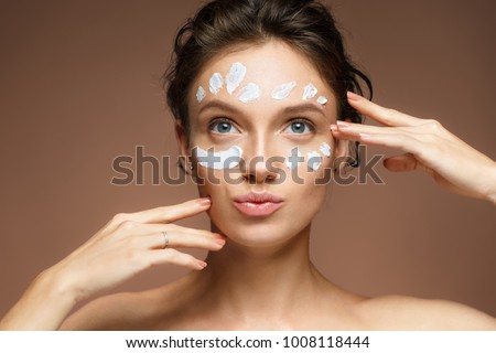 Young woman with moisturizing cream. Photo of beautiful brunette woman touching her face on brown background. Skin care concept
