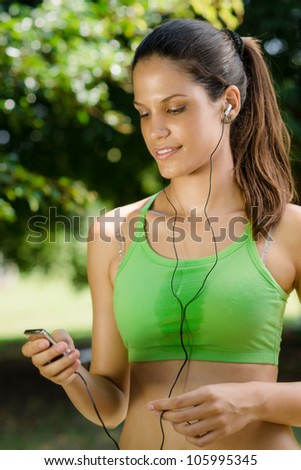 Young woman with mp3 player doing fitness in city park