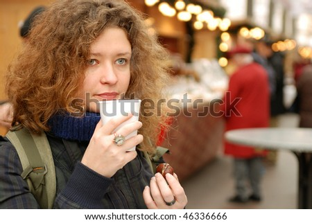 young woman with mulled wine and chestnut at christmass fair