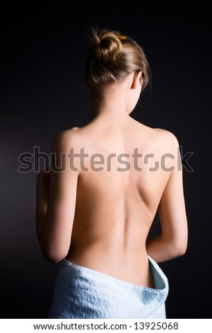 Young woman with naked back. On dark background.
