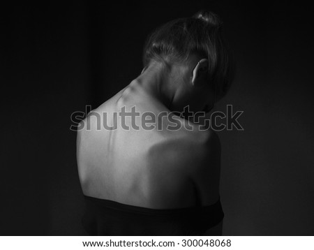 young woman with naked back over black background. sad girl