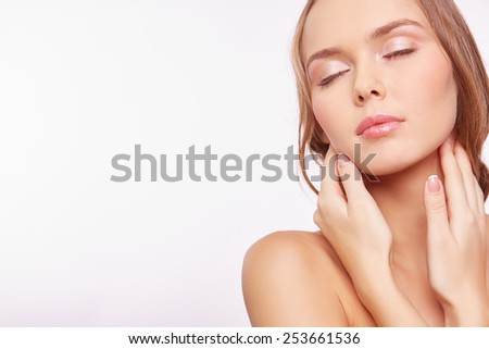 Young woman with natural makeup touching her face #253661536