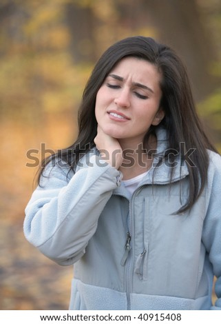 Young woman with neck pain outdoors in autumn