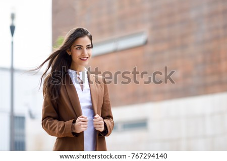 Young woman with nice hair in the wind standing in urban background. Businesswoman wearing formal wear with wavy hairstyle. Young girl with brown jacket and trousers.