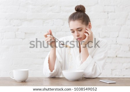 Young woman with no appetite, tired, bad mood and sleepy, sitting in the white loft kitchen, having unsavory unpalatable unappetizing breakfast