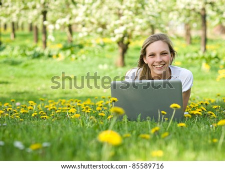 Young woman with notebook in park looking at camera