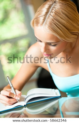 Young woman with notebook or organiser at home