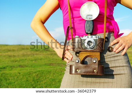 Young woman with old camera outdoor.