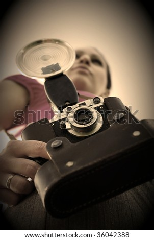 Young woman with old camera outdoor. Retro style.