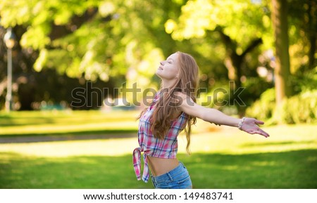 Young woman with open arms standing outdoors