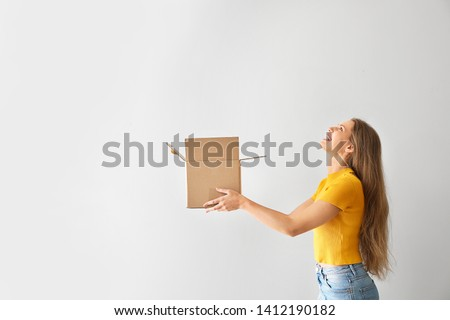 Young woman with open cardboard box on light background