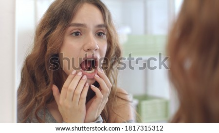 Young woman with opened mouth checking teeth in mirror in home bath room. Brunette woman looking mouth, teeth and smile front bathroom mirror. Teeth care, beauty and health concept