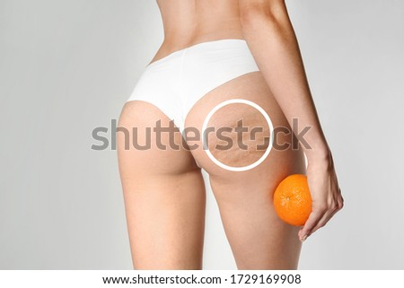 Young woman with orange on light background. Problem of cellulite Сток-фото ©