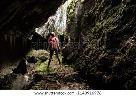 Young woman with orange travel backpack and lightern explores ancient fortress cave, view from back #1140916976