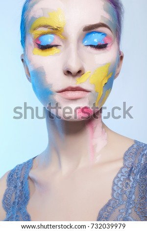 young woman with paint on her face. painted mask girl portrait #732039979