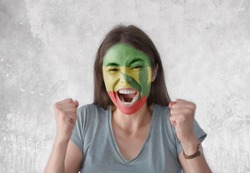 Young woman with painted flag of Rasta and open mouth looking energetic with fists up