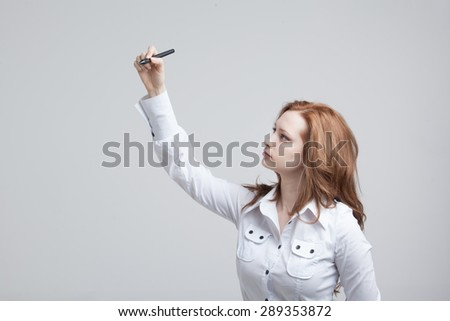 young woman with pen  writes or shows on grey background