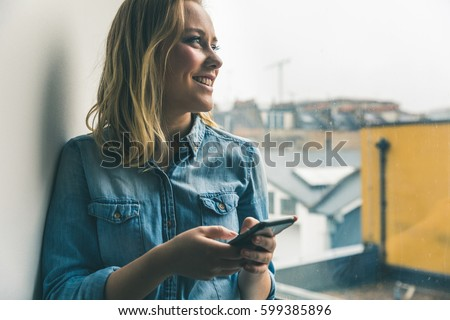 Young woman with phone looking out of window at home. Beautiful blond girl wearing denim shirt. Smiling happy face, lifestyle and technology concepts. Toned image