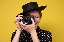 Young woman with photocamera making pictures. Studio shot on yellow wall.