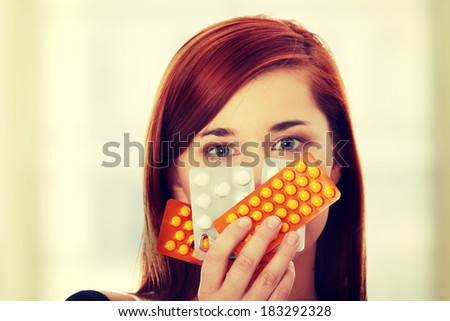 Young woman with pills - focus on pills