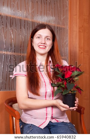 Young woman with Poinsettia flowers in flowering pot  at her home