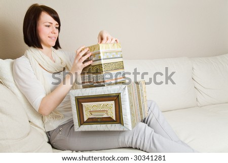 Young woman with presents in her living room