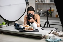 Young woman with professional camera taking food photo in studio