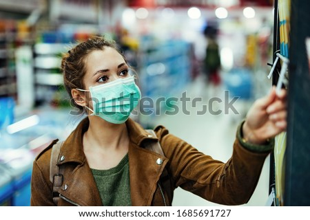 Young woman with protective mask on her face buying in supermarket during coronavirus pandemic.