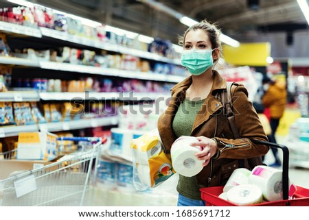 Young woman with protective mask shopping toilet paper and making supplies during virus pandemic.