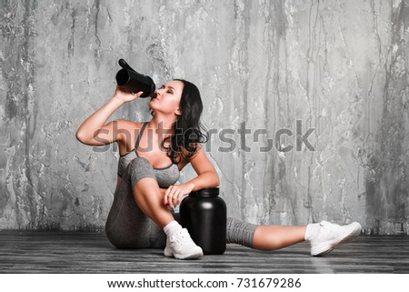 Young woman with protein shake bottle