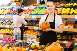 Young woman with pumpkin in hands and man on background on the supermarket