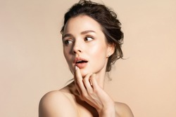 Young woman with pure skin feeling fear, wonder, surprise or shock beauty portrait on beige copy space. Pretty millennial girl with bare shoulder open mouth.