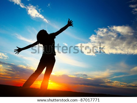 Young woman with raised hands on sunset sky background