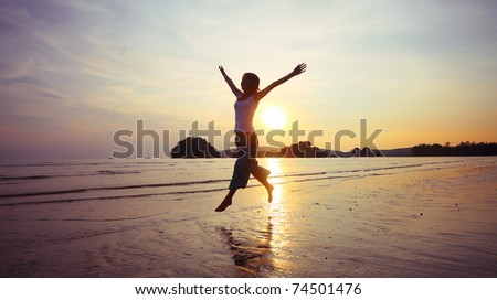 Young woman with raised hands running on wet sand - stock photo