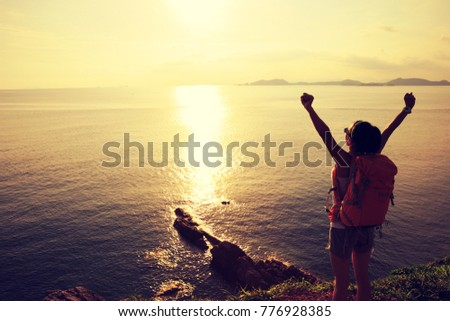 Young woman with raised hands standing at sunrise seaside mountain